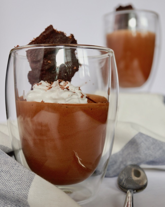 Two glass cups filled with chocolate mousse, garnished with whipped coconut and a chocolate biscuit