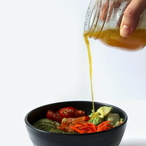 salad dressing being poured onto a salad