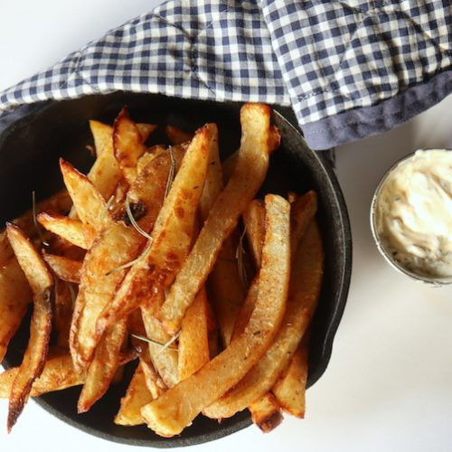 A small cast iron frying pan filled with french fries