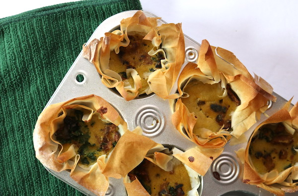 a muffin tin filled with individual mini quiches