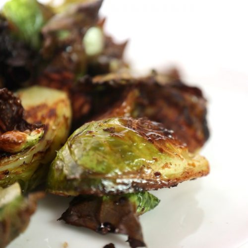 a white plate with crispy fried brussels sprouts with crispy brown bits